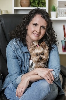 Dame adulte avec chien mignon assis sur une chaise