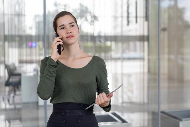 Dame d'affaires sérieuse concentrée sur appel