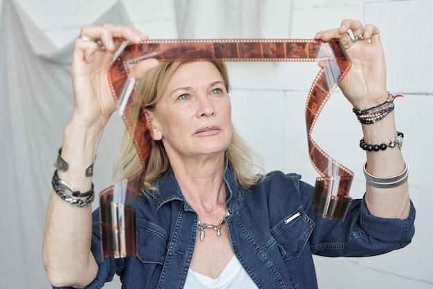 Dame d'âge mûr avec des bracelets regardant une bande de film sur la lumière tout en choisissant des images