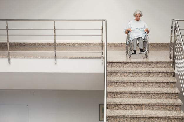 Une dame âgée en fauteuil roulant en haut des escaliers