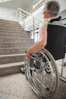Une dame âgée en fauteuil roulant levant les yeux