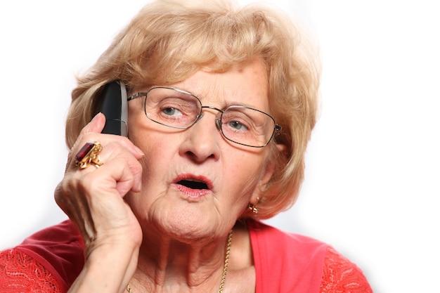 Une dame âgée parlant au téléphone sur fond blanc