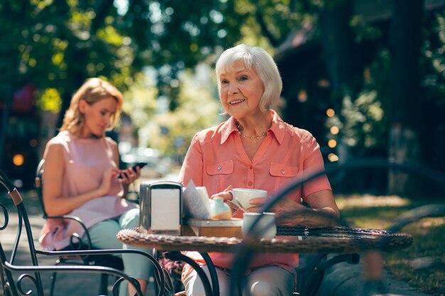 Dame âgée positive souriant et buvant du café au café de la rue