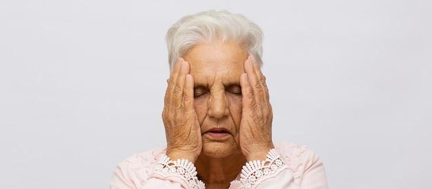 Dame âgée souffrant de maux de tête ou de fièvre tenant sa main sur son front, les yeux fermés de douleur, la tête et les épaules sur fond gris