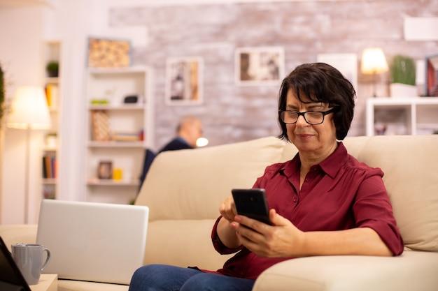 Dame âgée utilisant la technologie moderne dans sa maison. elle a un smartphone moderne dans ses mains