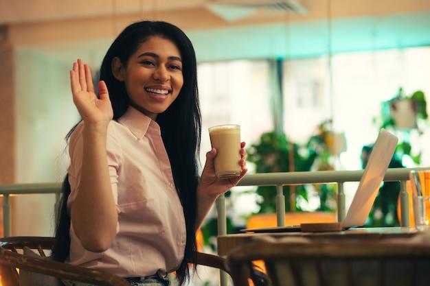 Dame Amicale Positive Assise Avec Un Verre De Latte Dans Un Café Et Souriant Tout En Regardant Au Loin Et En Agitant La Main Photo Premium