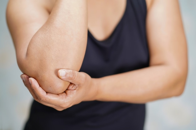 Une dame asiatique d'âge moyen touche et ressent une douleur au coude et au bras.