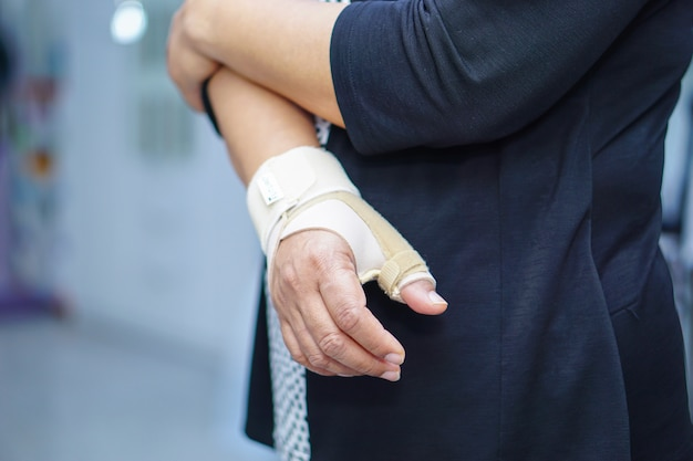 Une dame asiatique d'âge moyen utilise un bandage élastique pour traiter le syndrome de de quervain à la main et au doigt dans l'exercice de ses fonctions.