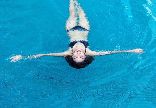 Dame asiatique dans la suite de natation jouant l'affichage de l'eau sur la piscine d'eau.