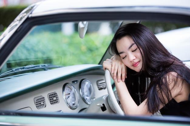 Dame asiatique souriante dans une voiture vintage