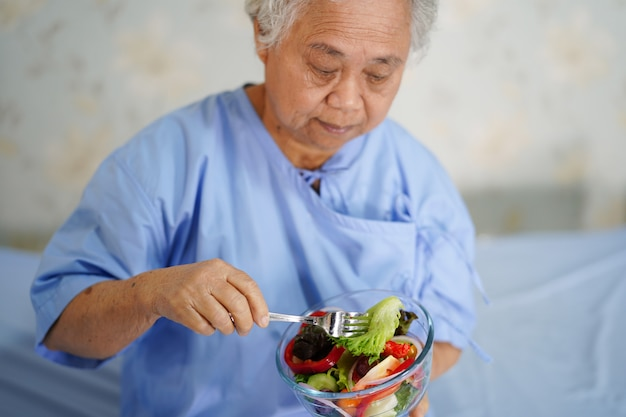 Dame asiatique tenant des aliments sains.