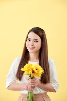 Dame asiatique tenant un bouquet de fleurs debout contre un mur