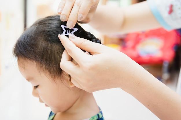 Dame asiatique tressant des cheveux pour enfant peu à la maison