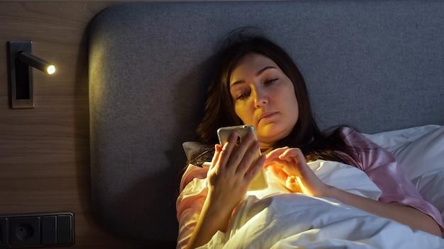 Une dame assez fatiguée en pyjama avec un téléphone avant de dormir est allongée dans son lit dans une chambre d'hôtel en gros plan