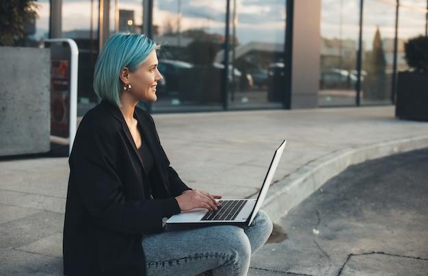 Dame aux cheveux bleus posant à l'extérieur alors qu'il était assis dans la rue et en tapant à l'ordinateur