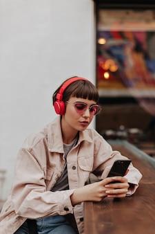 Dame aux cheveux courts en lunettes roses et tenue beige denim écoutant de la musique à l'extérieur