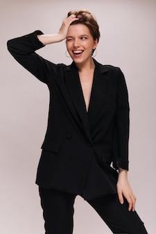 Dame aux cheveux courts en tenue noire clignotant sur fond blanc. charmante femme caucasienne en costume sombre largement souriant sur isolé