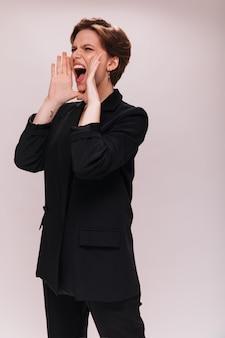Dame aux cheveux courts en tenue noire crie sur fond blanc. jeune femme en veste sombre et pantalon hurle en toile de fond isolée