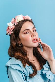 Dame aux cheveux noirs aux lèvres charnues. fille aux yeux verts avec de longs cils et en couronne de fleurs posant sur un mur bleu.