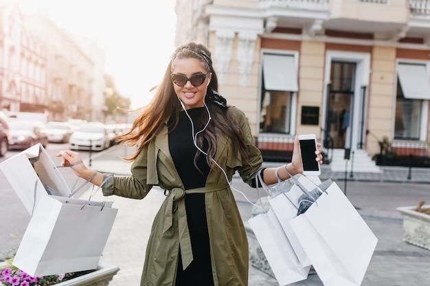 Dame aux cheveux noirs glamour avec smartphone marchant dans la rue après les achats du matin