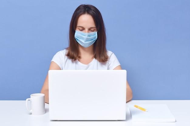 Dame aux cheveux noirs portant un t-shirt décontracté et un masque de protection médical travaillant devant un écran d'ordinateur portable, semble concentrée, étudiante faisant une tâche universitaire en ligne, éducation.