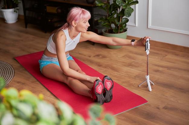 Une dame aux cheveux roses ajuste son smartphone en se préparant à filmer un didacticiel vidéo à la maison