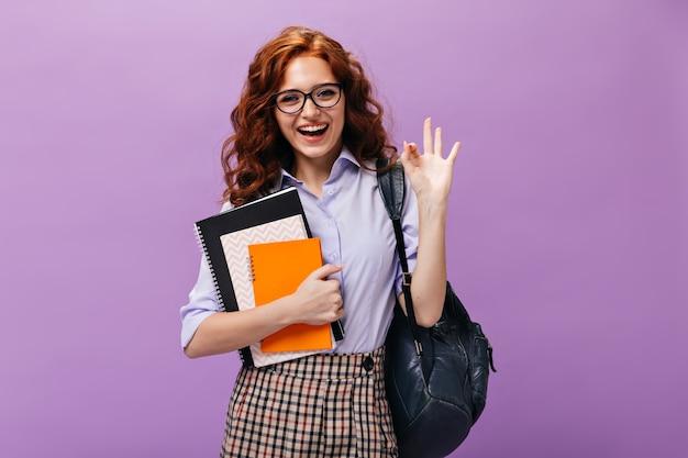 Une dame aux cheveux rouges à lunettes tient des livres et montre un signe ok