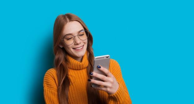 Dame aux cheveux rouges avec des taches de rousseur bavardant sur mobile dans un mur de studio bleu avec espace libre