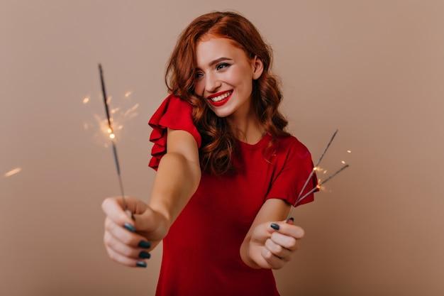 Dame bien habillée ludique célébrant le nouvel an. merveilleuse fille au gingembre avec des lumières du bengale s'amusant à noël.