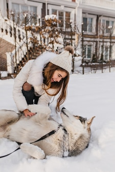 Dame blanche inspirée au chapeau s'amusant avec un husky sur la neige. photo extérieure d'une jeune femme en riant jouant avec son chien dans la cour.
