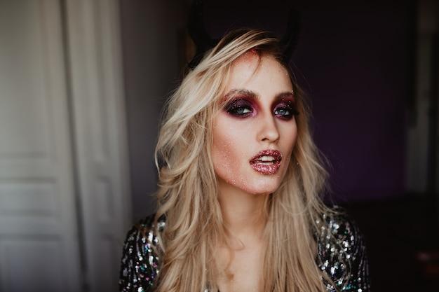 Dame blanche sensuelle avec des ombres à paupières violettes brillantes. femme blonde sérieuse avec un maquillage sombre.