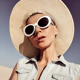 Dame blonde en accessoires de mode. chapeau et lunettes de soleil. ambiance de plage uniquement