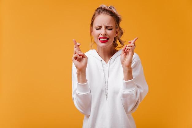 Dame blonde anxieuse et émotionnelle en sweat à capuche avec des lèvres brillantes pense à son désir le plus profond