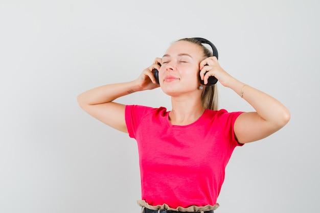 Dame blonde appréciant la musique avec des écouteurs en t-shirt rose et à la ravie, vue de face.