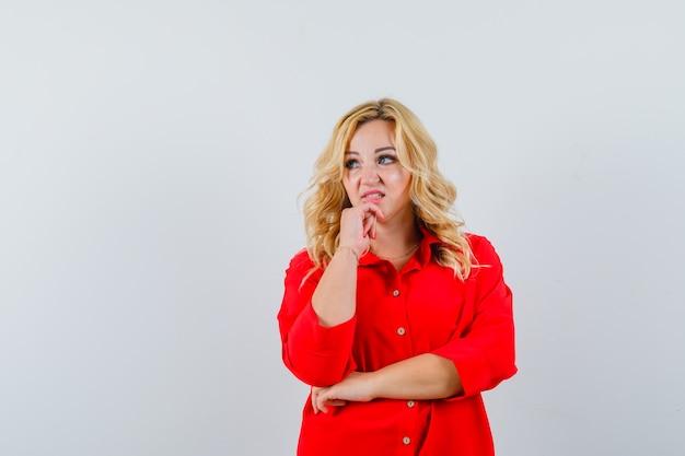 Dame blonde en chemise rouge à côté et à l'espace confus pour le texte