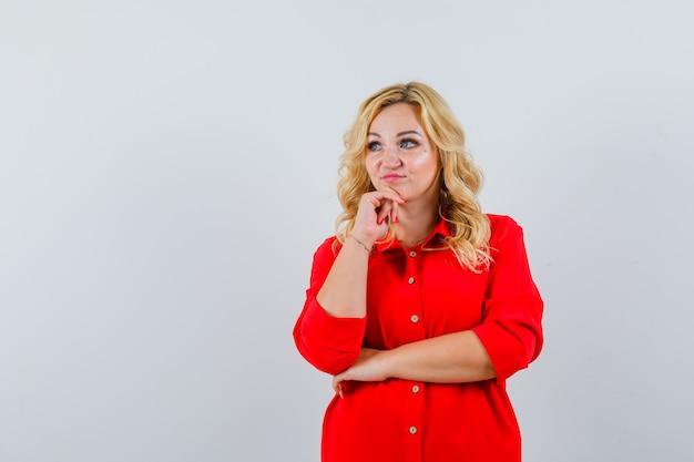 Dame blonde en chemise rouge à la recherche de suite et à la pensive