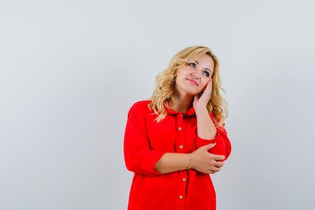 Dame blonde en chemise rouge touchant son visage et à la recherche d'un bel espace pour le texte