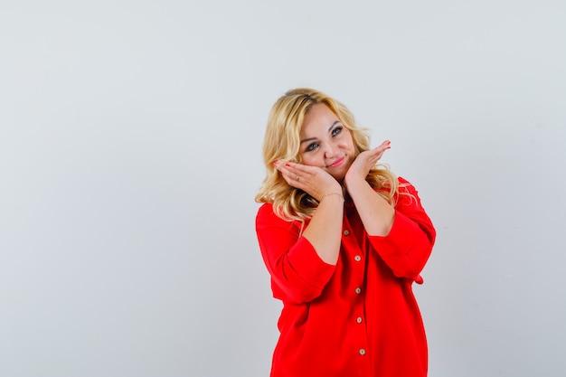 Dame blonde en chemise rouge touchant son visage et à la recherche d'un espace mignon pour le texte