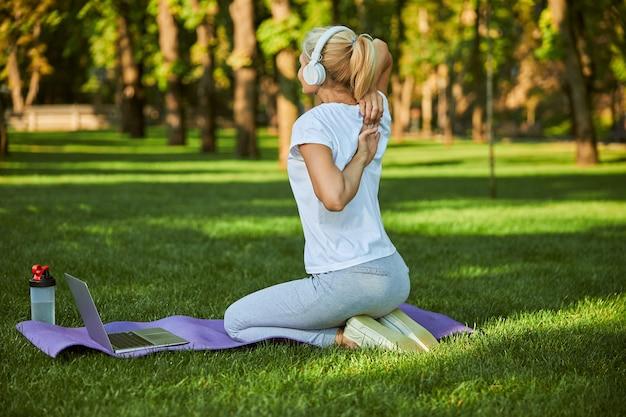 Dame blonde dans des écouteurs sans fil assis sur un tapis de yoga avec ordinateur portable et faire de l'exercice