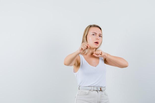 Dame blonde debout dans la lutte pose en maillot, pantalon et à la méchante, vue de face.