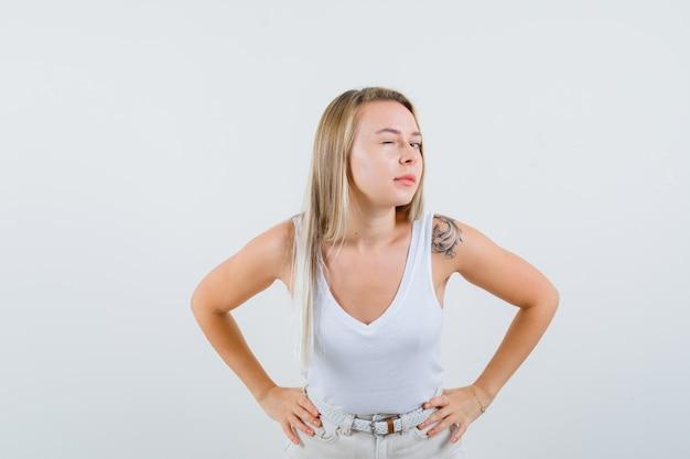 Dame blonde debout pour entendre clairement en maillot, pantalon et curieux, vue de face.