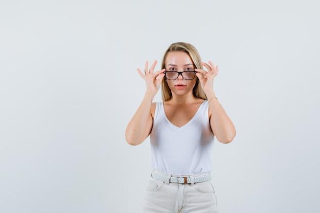 Dame blonde décollant des lunettes en maillot, pantalon et à la recherche raisonnable