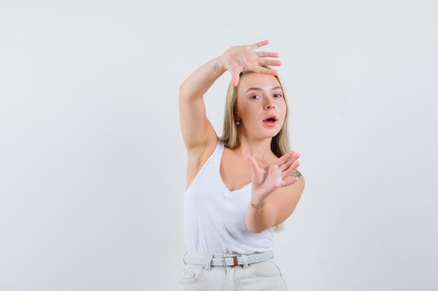 Dame blonde faisant le geste du cadre en maillot, pantalon et à la vue de face, confiant.