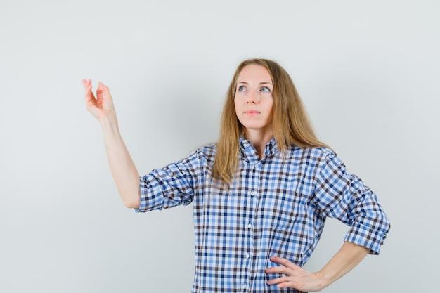 Dame blonde levant le bras tout en regardant en chemise et à la recherche d'espoir,