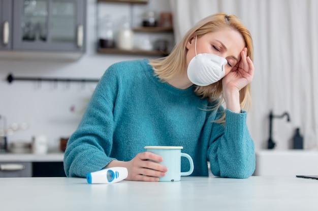 Dame blonde en masque avec tasse de thé chaud et thermomètre à table de cuisine