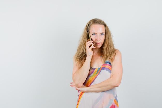 Dame blonde parlant au téléphone mobile en robe d'été et à la pensif.