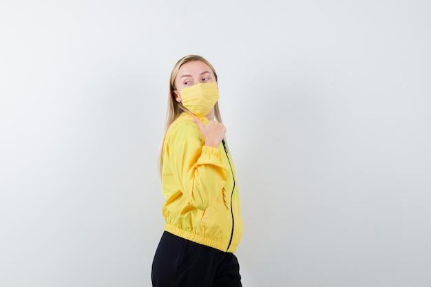 Dame blonde pointant vers l'arrière avec le pouce en survêtement, masque et à la recherche de curiosité.