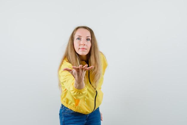 Dame blonde qui s'étend de la main de manière interrogative en veste, jeans,