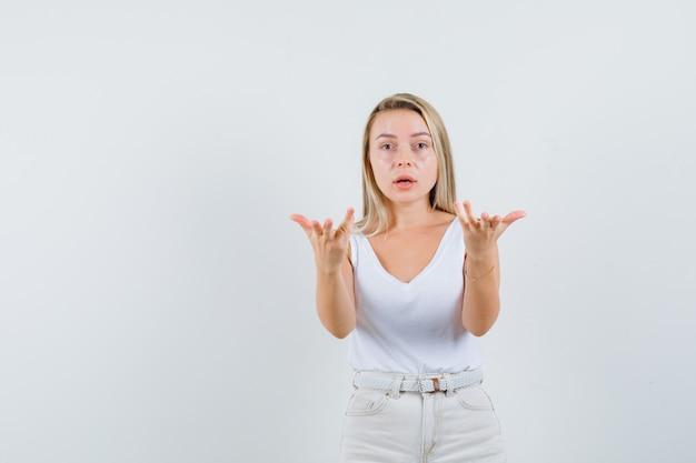 Dame blonde qui s'étend les mains en geste de questionnement en maillot, pantalon, vue de face.
