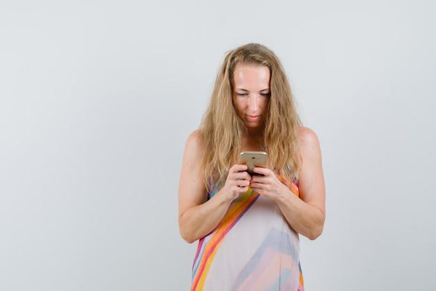 Dame blonde en robe d'été tapant sur téléphone mobile et à la recherche de occupé